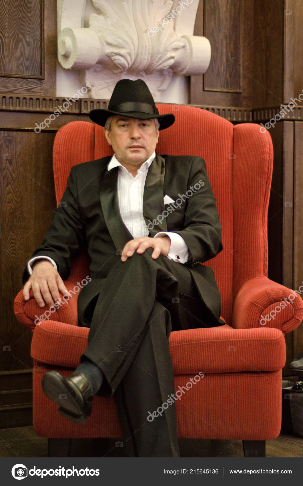 22001102138 Šedá vlasy starší gangster v interiéru. Šedá vlasy starší mafián na sobě  černý oblek a klobouk sedí v červené křeslo starého interiéru — Fotografie  od ...