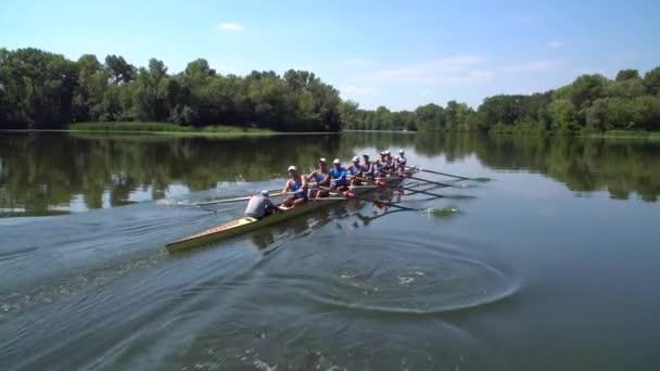 Rudern Sommer Teamtraining. 8 Athleten Ruderer in einem Boot im Fluss Dnipro. Stadtgebiet in Kiew, Ukraine