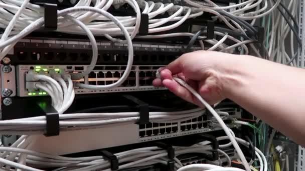 Russland, Moskau - 15. Mai 2018: Ingenieur arbeitet in einem Rechenzentrum. männliche Hand steckt das Datumskabel in den Internet-Router. rg-45