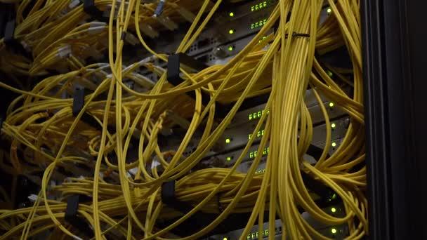 Video enthält Rauschen. Gelbe Glasfaserkabel nähern sich dem Rechenzentrum. Telekommunikations-Breitband. Blinkende grüne LED-Lichter. Video enthält Lärm.