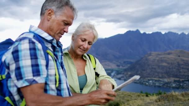 Fit retired Caucasian couple reading map on the hike of Mt Aspiring Lake Wakatipu New Zealand