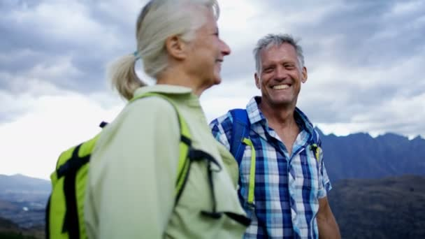 Loving retired Caucasian couple with rucksacks enjoying togetherness trekking landscape of The Remarkables Otago New Zealand
