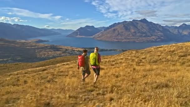 Aerial drone of young Caucasian adventure hikers with rucksack enjoying hiking in nature of Lake Wakatipu New Zealand