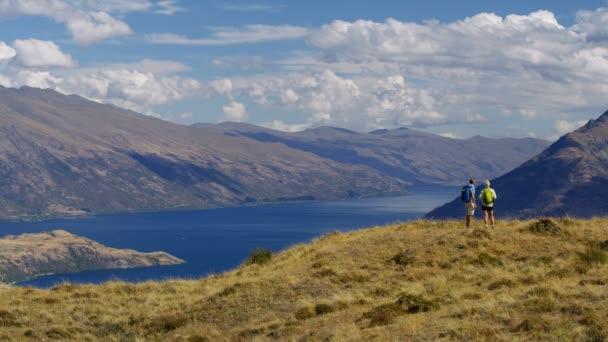 Healthy Caucasian male and female seniors trekking to keep fit Mount Aspiring Lake Wakatipu New Zealand