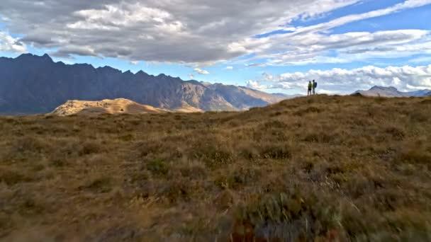Aerial drone of active retired Caucasian couple with binoculars enjoying retirement hiking of Mt Aspiring Lake Wakatipu New Zealand