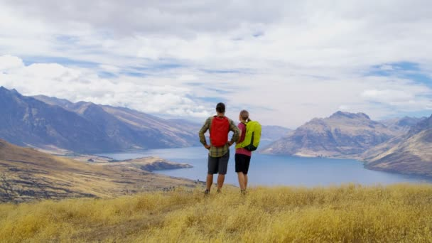 Young active healthy Caucasian male and female trekking nature of The Remarkables Lake Wakatipu New Zealand