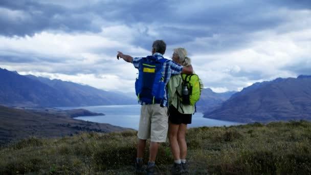 Loving active senior Caucasian couple wearing casual clothing enjoying walking outdoor of Lake Wakatipu Queenstown New Zealand