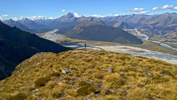 Aerial drone view of Caucasian adventure female hiker with backpack achieving expedition goals in Fjordland National Park New Zealand