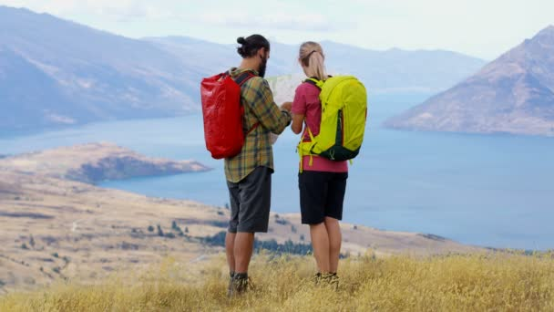 Fit Caucasian adventure hikers with backpacks reading map on hike of Fjordland The Remarkables Lake Wakatipu New Zealand