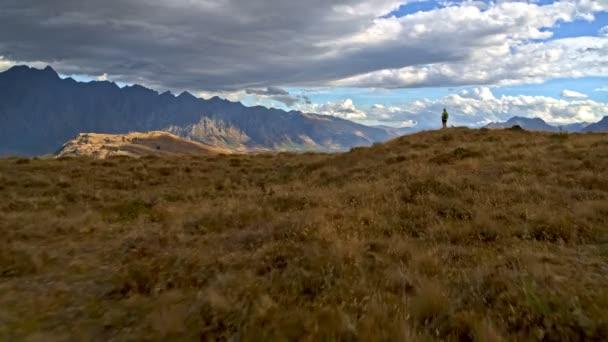 Aerial drone of active Caucasian senior female with binoculars trekking to keep healthy of Mt Aspiring Lake Wakatipu New Zealand