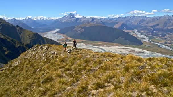 Aerial drone of young Caucasian adventure hikers with backpacks walking in nature of Fjordland National Park New Zealand