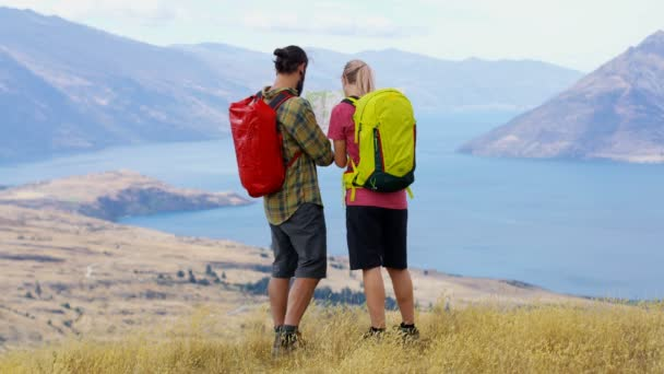 Fit Caucasian adventure hikers planning tour reading map of The Remarkables Lake Wakatipu New Zealand