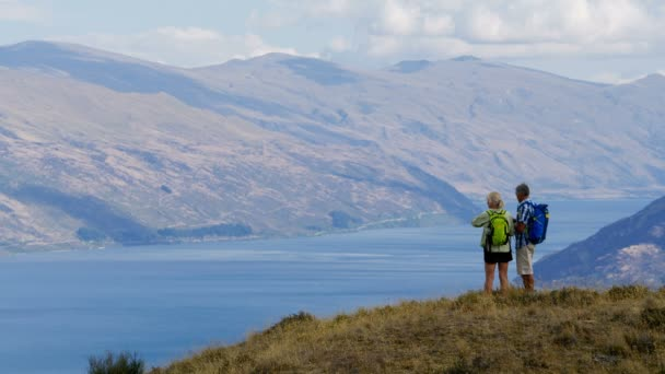 Fit retired Caucasian couple with binoculars enjoying vacation hiking of The Remarkables Lake Wakatipu New Zealand