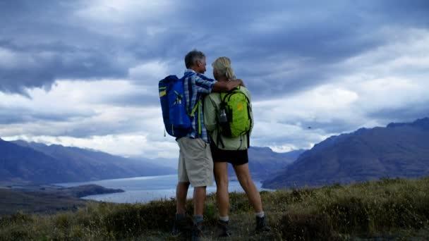 Happy Caucasian male and female seniors trekking enjoying retirement Mount Aspiring Lake Wakatipu New Zealand