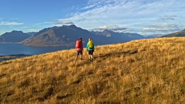 Aerial drone of active Caucasian hikers with backpacks enjoying hiking in wilderness of Mount Aspiring Lake Wakatipu New Zealand