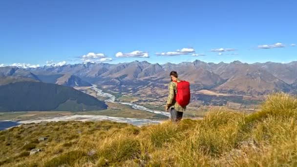 Aerial drone view of active young Caucasian male hiker outdoors on his vacation hiking Fjordland National Park New Zealand