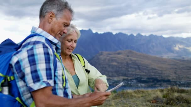 Active fit Caucasian male and female senior travellers enjoying their hiking and planning tour reading map of The Remarkables Lake Wakatipu New Zealand