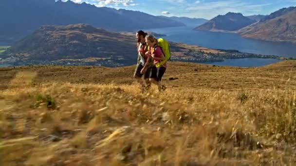 Aerial drone of active healthy Caucasian male and female trekking landscape of Mount Aspiring Lake Wakatipu New Zealand