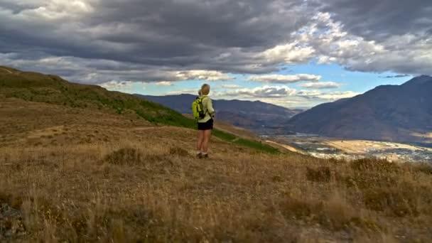 Aerial drone of healthy Caucasian senior female trekking using binoculars The Remarkables Lake Wakatipu New Zealand