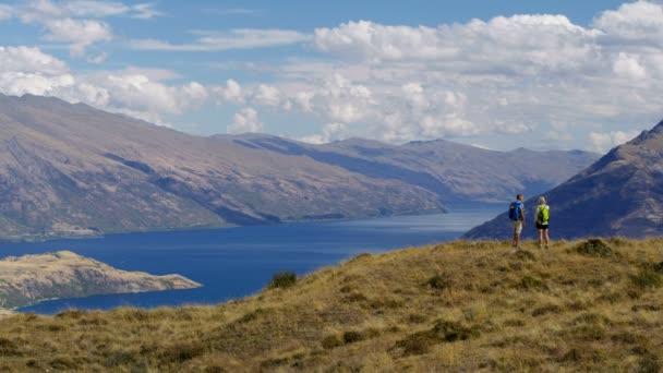 Active retired Caucasian couple with rucksacks enjoying trekking wilderness of The Remarkables Lake Wakatipu New Zealand