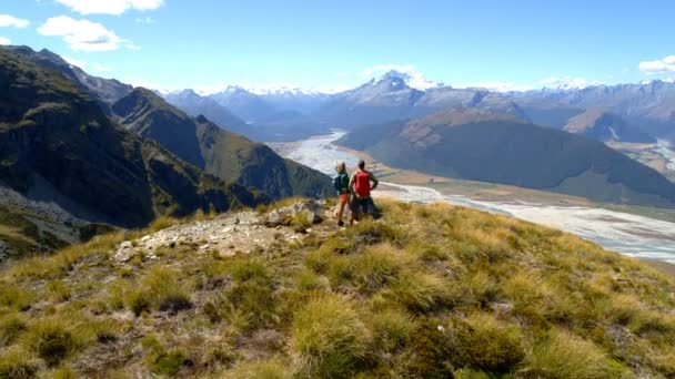 Aerial drone of young Caucasian adventure hikers with rucksacks enjoying trekking in landscape of South Island New Zealand