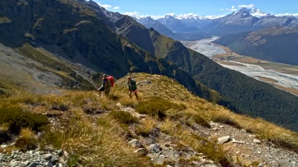 Aerial drone view of fit Caucasian adventure male and female trekking landscape of Mount Aspiring South Island New Zealand