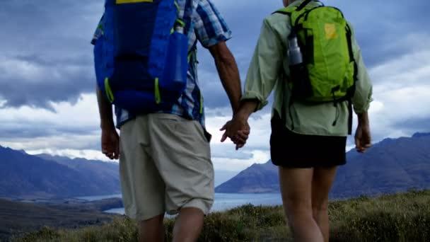 Loving fit Caucasian male and female senior travellers hiking holding hands Mount Aspiring Lake Wakatipu New Zealand