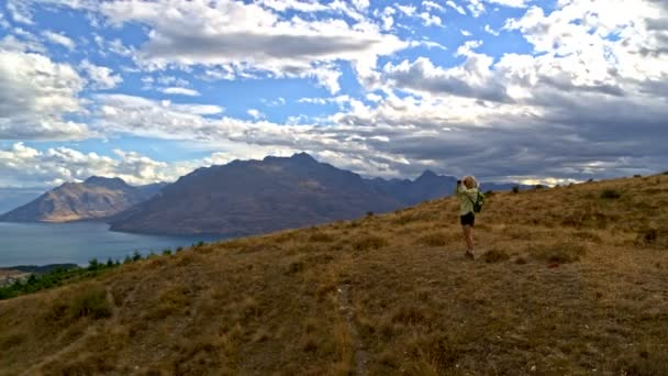 Aerial drone of fit mature Caucasian female trekking watching landscape with binoculars outdoor The Remarkables Otago New Zealand