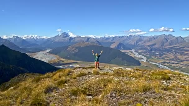 Aerial drone of confident Caucasian female traveller celebrating achievement goal on the top of mountain Fjordland National Park New Zealand