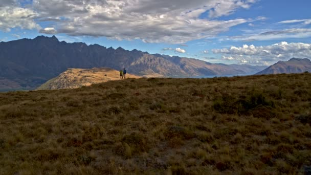 Aerial drone of fit mature Caucasian couple trekking watching landscape with binoculars outdoor The Remarkables Otago New Zealand