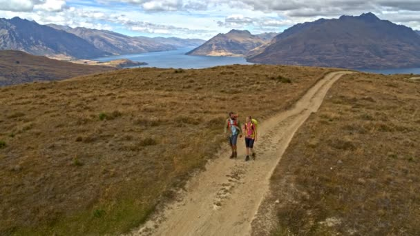 Aerial drone view of active Caucasian travellers outdoor enjoying hiking on mountain path of Fjordland Lake Wakatipu New Zealand