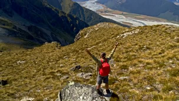 Aerial drone of Caucasian male and female celebrating achieving goals with raised hands on adventure trip in Mt Aspiring New Zealand