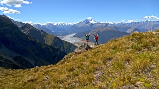 Aerial drone of Caucasian male and female hikers celebrating achieving success on top of mountain in Mount Aspiring New Zealand
