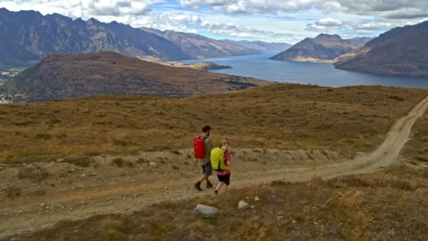 Aerial drone view of happy Caucasian adventure couple walking on mountain road of The Remarkables Fjordland National Park New Zealand