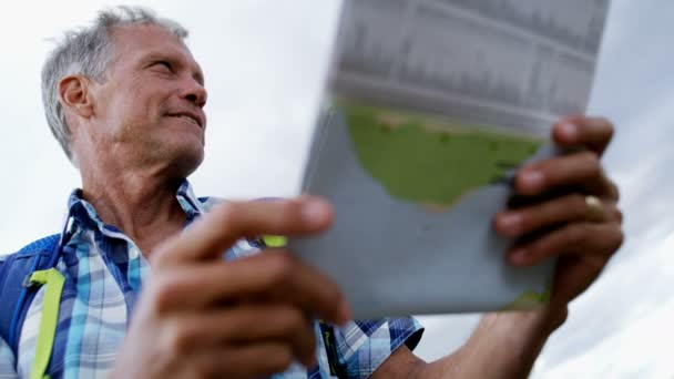 Healthy retired Caucasian male enjoying vacation planning trip reading map of The Remarkables Lake Wakatipu New Zealand