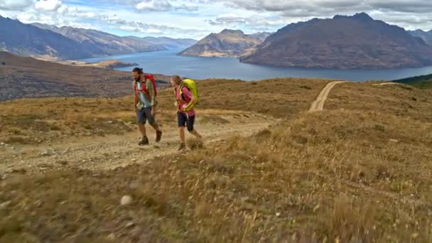 Aerial drone of young active Caucasian adventure hikers trekking on mountain path Mount Aspiring Lake Wakatipu New Zealand