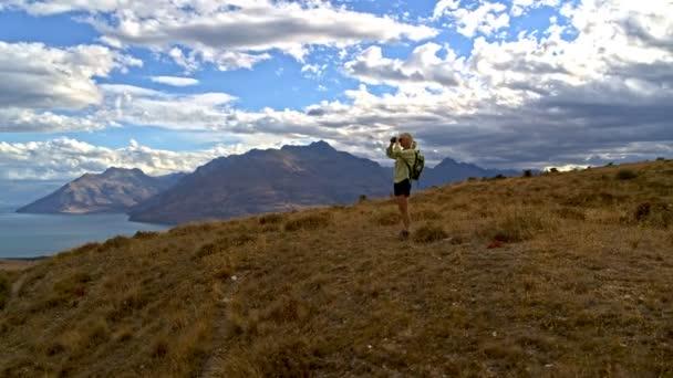 Aerial of Caucasian senior female traveler hiking using binoculars outdoor Mt Aspiring Lake Wakatipu New Zealand
