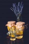 selective focus of lavender and various jars with honey on black background