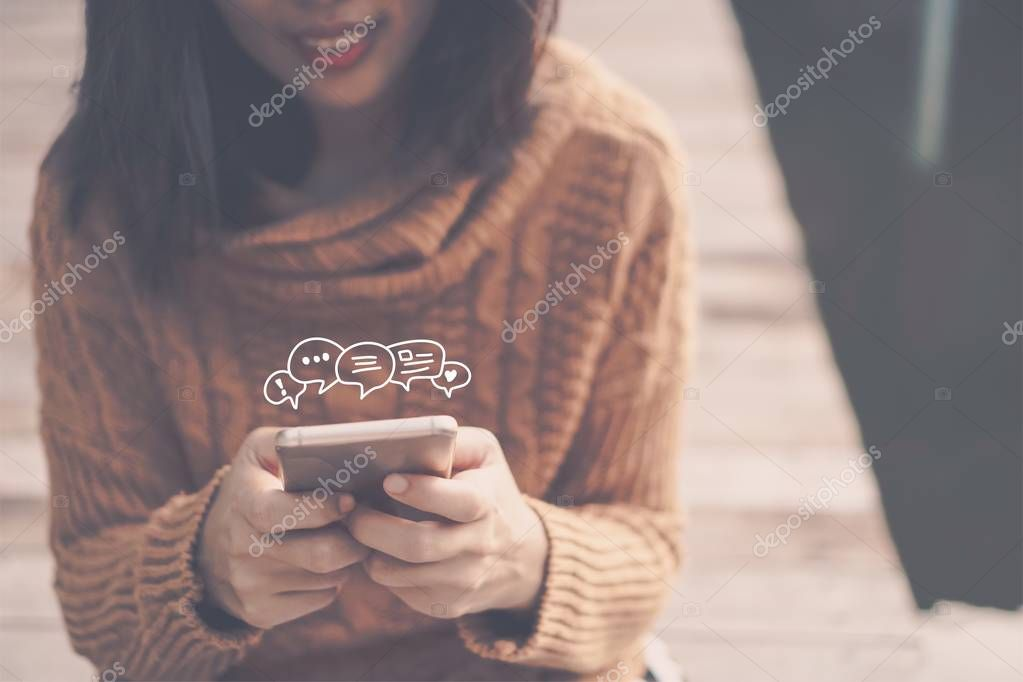 Woman hand using smartphone with chat icon in cafe shop background. Business communication social network concept.
