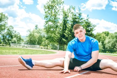 Man doing stretching exercises on open air athletics track field during hot summer day. Toned image.
