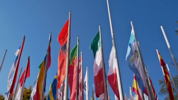 Several flagpoles with different flags in the wind before blue sky as background