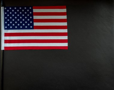 little american flag on dark leather surface with space for text studio light