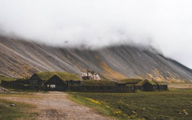 old viking village in iceland with foggy hill. old wooden buildings covered grass
