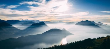 aerial view of mountain scenery in the swiss alps during late autumn, colored pinetrees and blue Lake Lucerne covered in fog seen from rigi switzerland