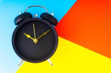 Clock on colorful background with selective focus and crop fragment. Copy space concept