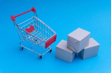 Shopping cart and box on blue background, business and shopping concept. Selective focus