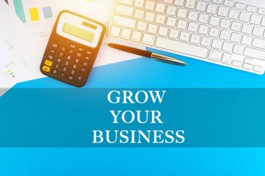 Flat lay view of office workspace with keyboard, pen, paperwork and words GROW YOUR BUSINESS. Business concept
