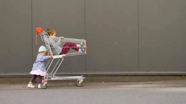 Little girl pushing shopping cart with brother sitting in it. Children entertainments while waiting for parents from shopping. LIttle hipster with shopping cart near supermarket. Conceptual.