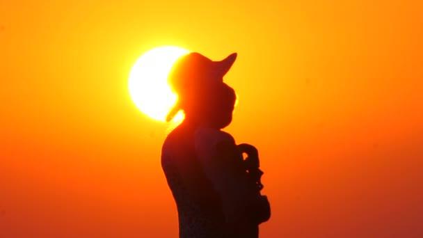 Půvabná matka s dítětem. Baby na matkách má ruce na pozadí slunce. Siluety rodiček s dítětem na pozadí se západem slunce. Šťastná rodina. Jedna dětská rodina. Jedna nadřazená rodina.