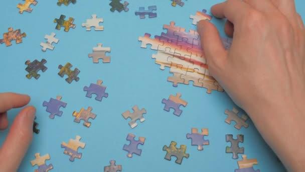 Skupina hádanek, ruce na pozadí modrého stolu. Logická hra, předškolní výchova. Puzzle kousky a ruce detailní. Koncept úkolu a dílčího úkolu. Zábava, koníček. Koncept týmové práce